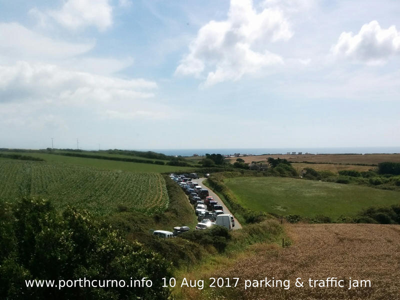 Cars parked on pavement on road to Porthcurno adding to traffic jam